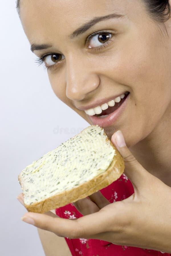 Fille mangeant la part du pain image stock