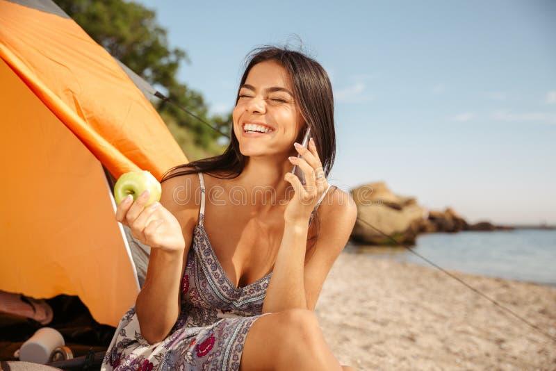 Fille mangeant la pomme et parlant au téléphone à la plage photo libre de droits
