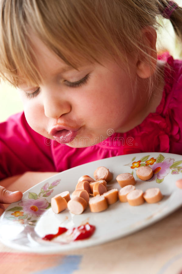 Fille mangeant la saucisse   photographie stock