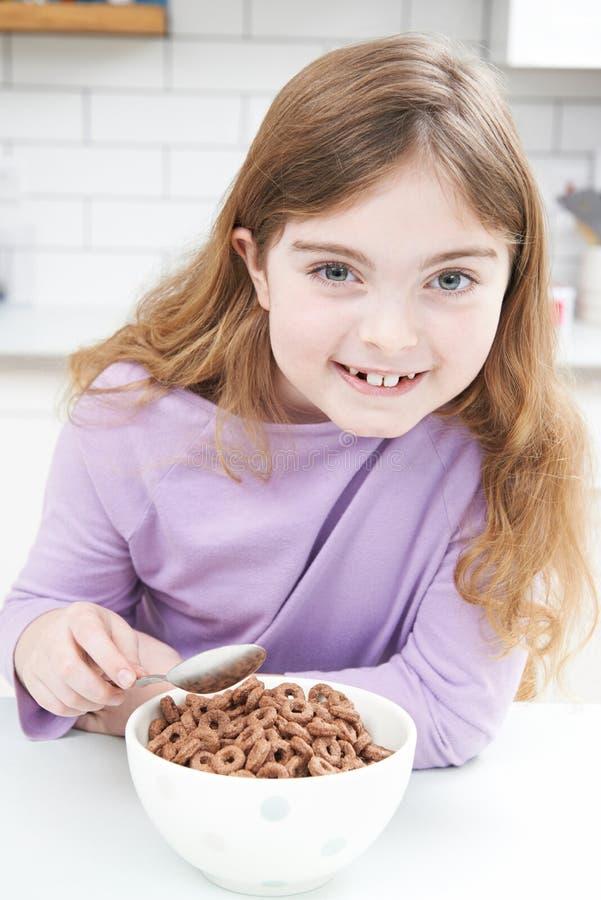 Fille mangeant le bol de céréale de petit déjeuner sucrée dans la cuisine image libre de droits