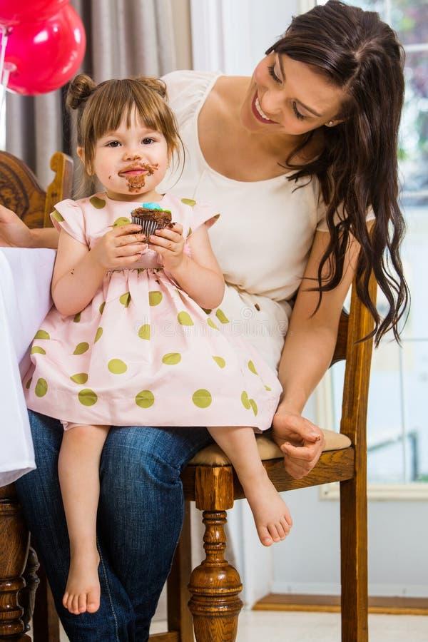 Fille mangeant le petit gâteau tout en se reposant sur le recouvrement de la mère images stock