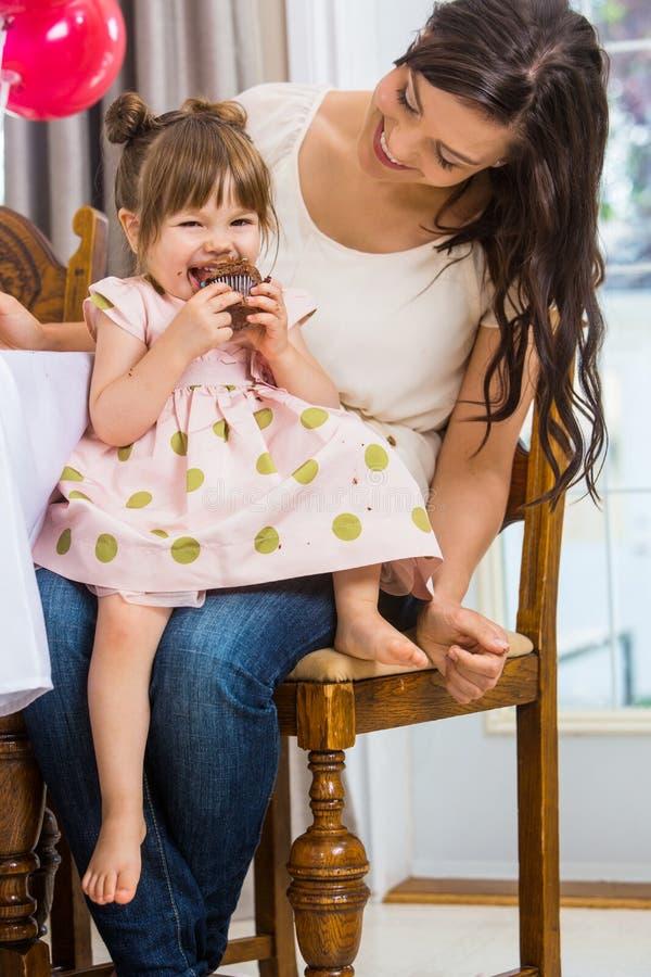 Fille mangeant le petit gâteau tout en se reposant sur le recouvrement de la mère image stock