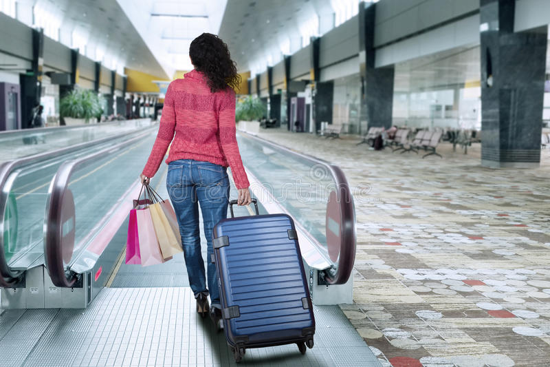 Fille marchant à l'escalator à l'aéroport photos libres de droits
