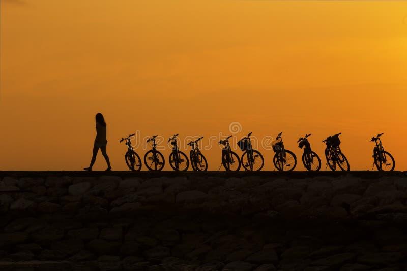Fille marchant après le vélo à la jetée pendant le lever de soleil photos stock
