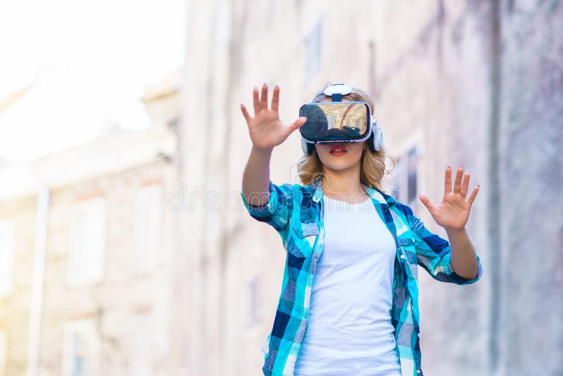 Fille marchant dans la rue dans le casque augmenté de réalité Réalité virtuelle et concept futuriste de technologie photographie stock libre de droits