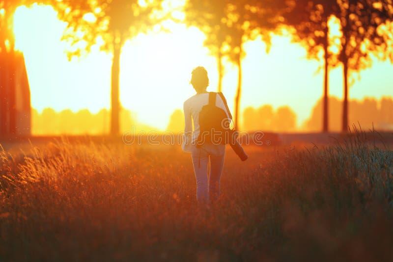 Fille marchant dans le coucher du soleil photos stock