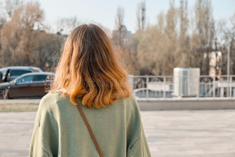 Fille marchant de retour avec les cheveux rouges bruns dans le chandail vert, journée de printemps ensoleillée de fond, l'espace  photographie stock