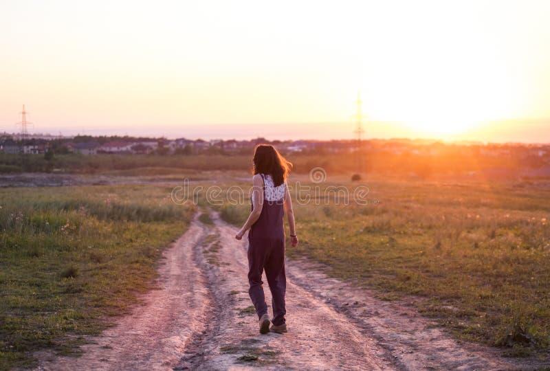 Fille marchant le long de la route de campagne au beau coucher du soleil photographie stock libre de droits