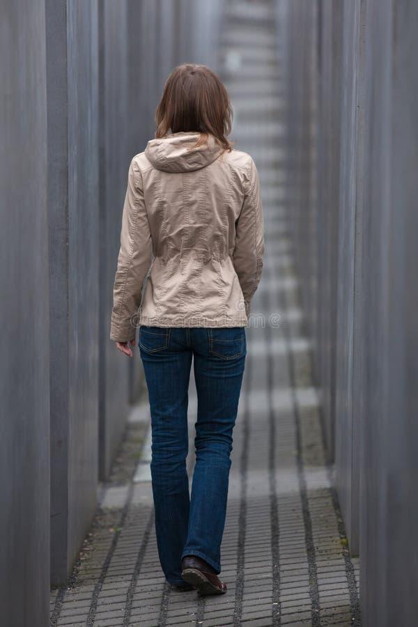 Fille marchant loin par le couloir gris image stock