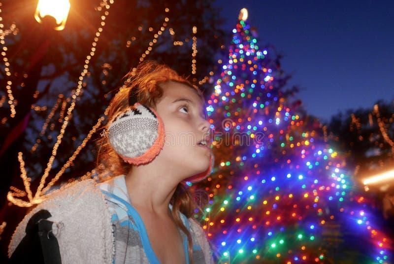 Fille marchant par un affichage de lumières de Noël la nuit photos libres de droits
