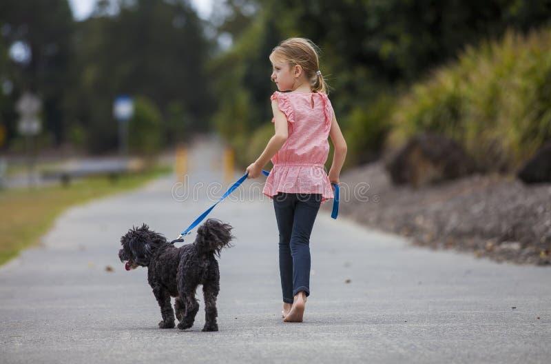 Fille marchant son chien photo stock