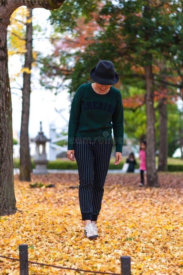 Fille marchant sur Autumn Leaves images libres de droits