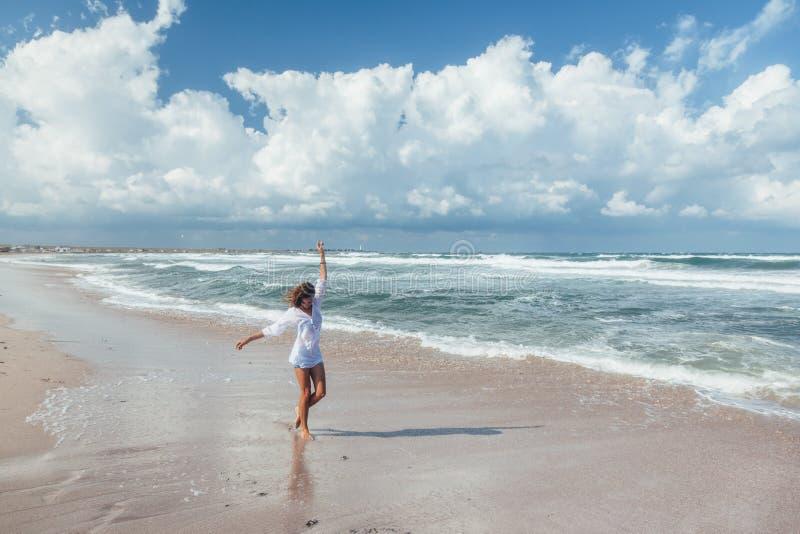 Fille marchant sur la plage image stock