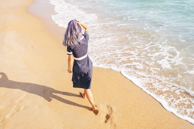 Fille marchant sur la plage près de la mer photo stock