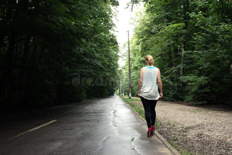 Fille marchant sur la route photos libres de droits