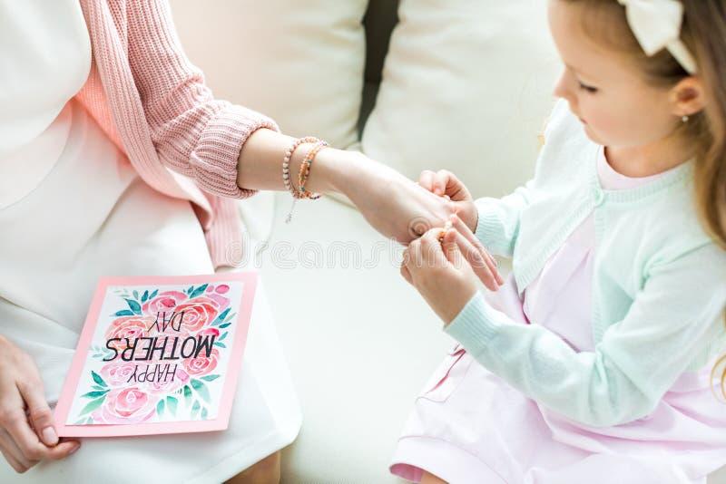 Fille mettant des bijoux sur la mère photos libres de droits
