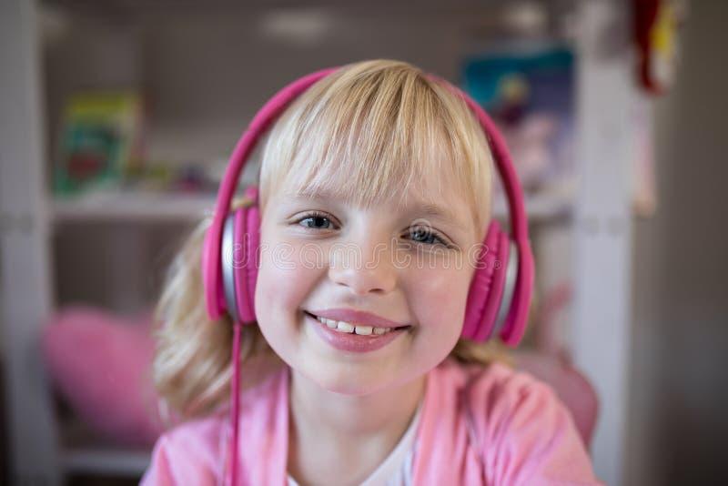 Fille mignonne écoutant les écouteurs roses photographie stock