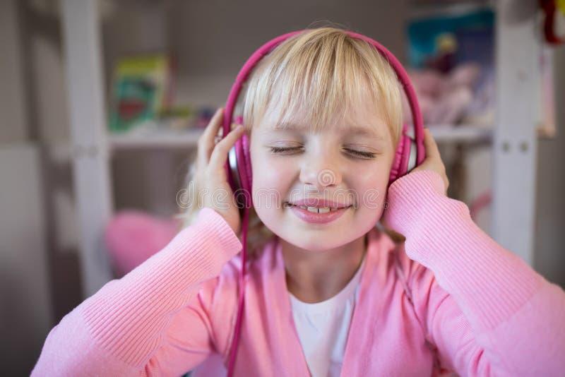 Fille mignonne écoutant les écouteurs roses photos stock