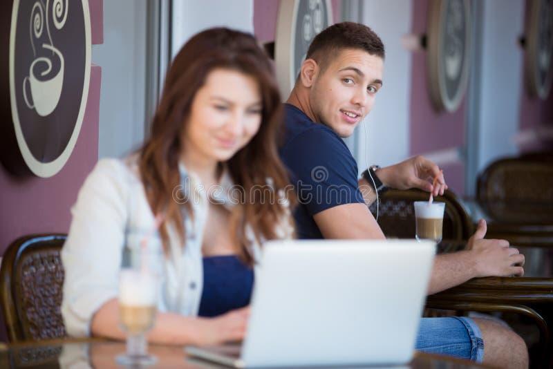Fille mignonne admirative de jeune homme dans un café image libre de droits