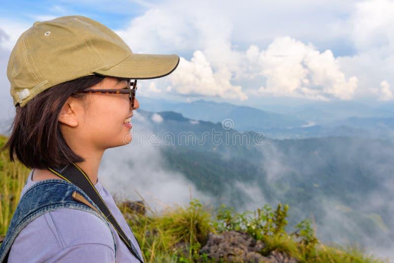 Fille mignonne asiatique d'ados de randonneur regardant la nature images stock