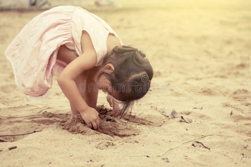 Fille mignonne asiatique d'enfant petite jouant avec le sable dans le terrain de jeu photos libres de droits