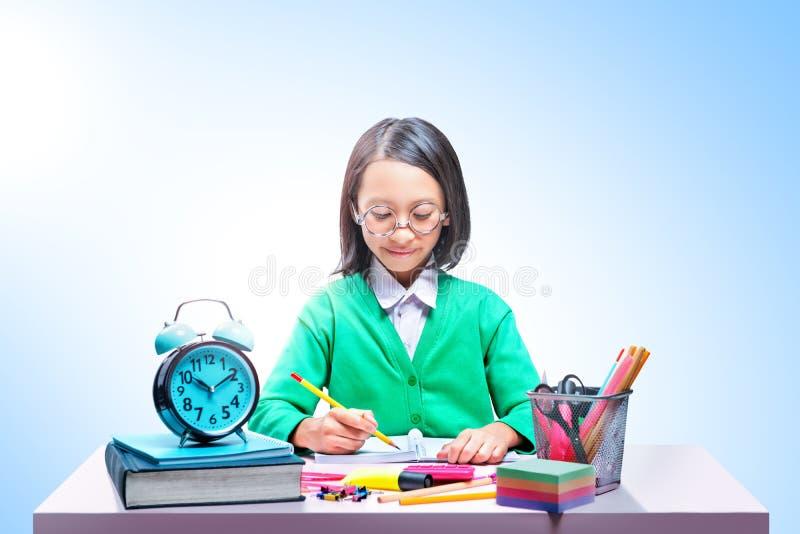 Fille mignonne asiatique en verres apprenant avec l'école stationnaire sur le bureau image stock
