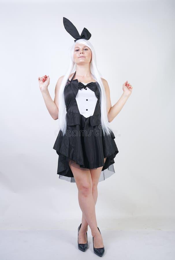 Fille mignonne avec de longs cheveux blancs avec des oreilles de lapin dans le costume de lapin sur le fond blanc dans le studio  photo stock