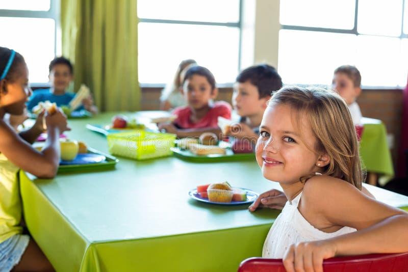 Fille mignonne avec des camarades de classe ayant le repas image libre de droits