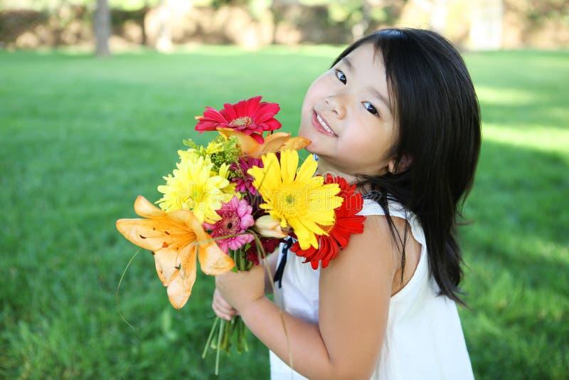 Fille mignonne avec des fleurs photographie stock libre de droits