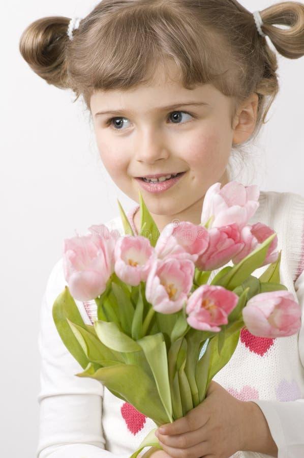 Fille mignonne avec des tulipes photo stock