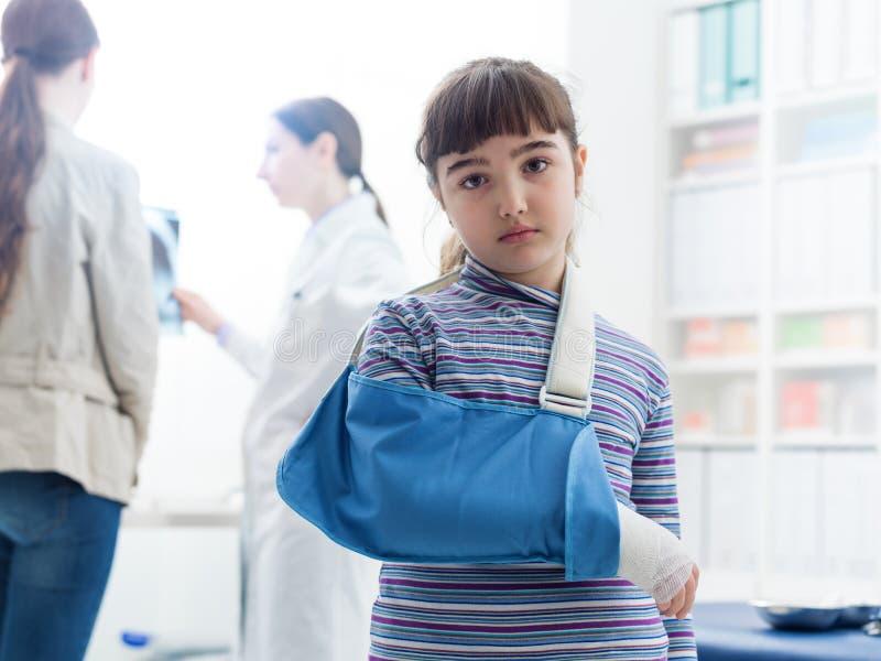Fille mignonne avec l'accolade de bras dans le bureau du docteur image libre de droits