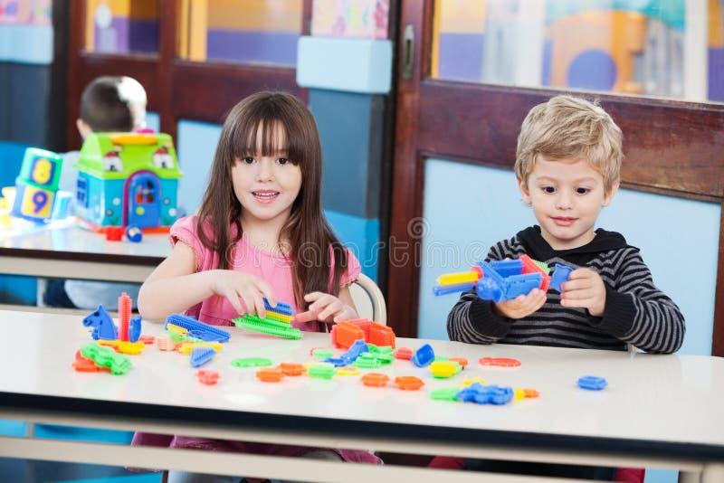 Fille mignonne avec l'ami jouant des blocs au bureau dedans image libre de droits