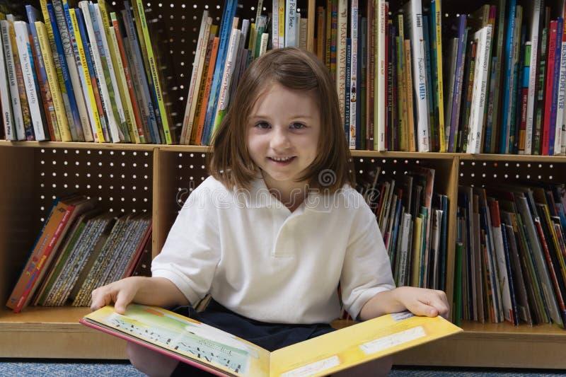 Fille mignonne avec le livre dans la bibliothèque photo libre de droits