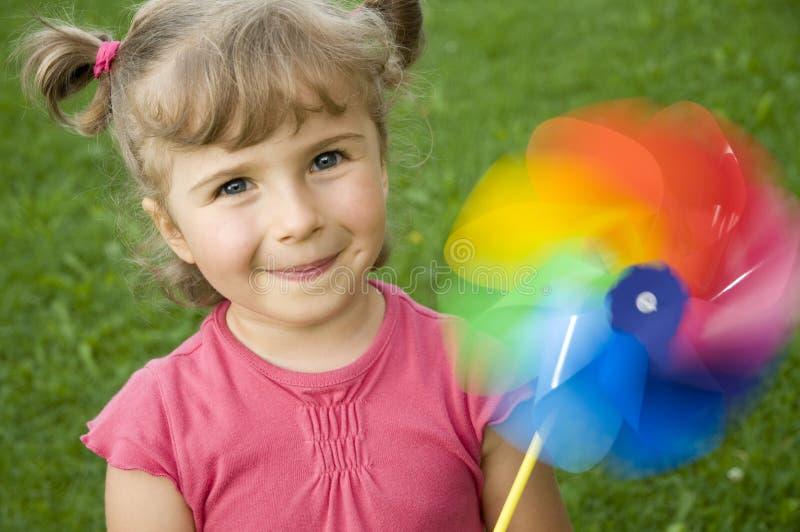 Fille mignonne avec peu de moulin à vent photographie stock libre de droits