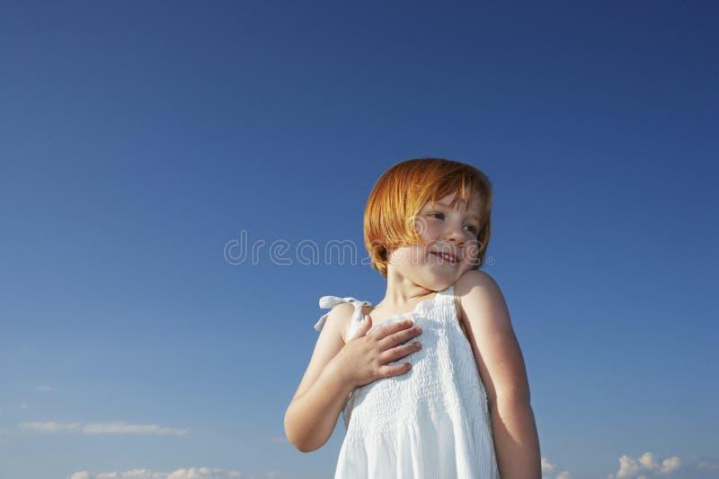 Fille mignonne avec plaisir regardant loin contre le ciel bleu photo stock