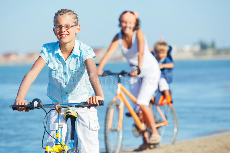 Fille mignonne avec ses vélos de conduite de mère et de frère photographie stock libre de droits