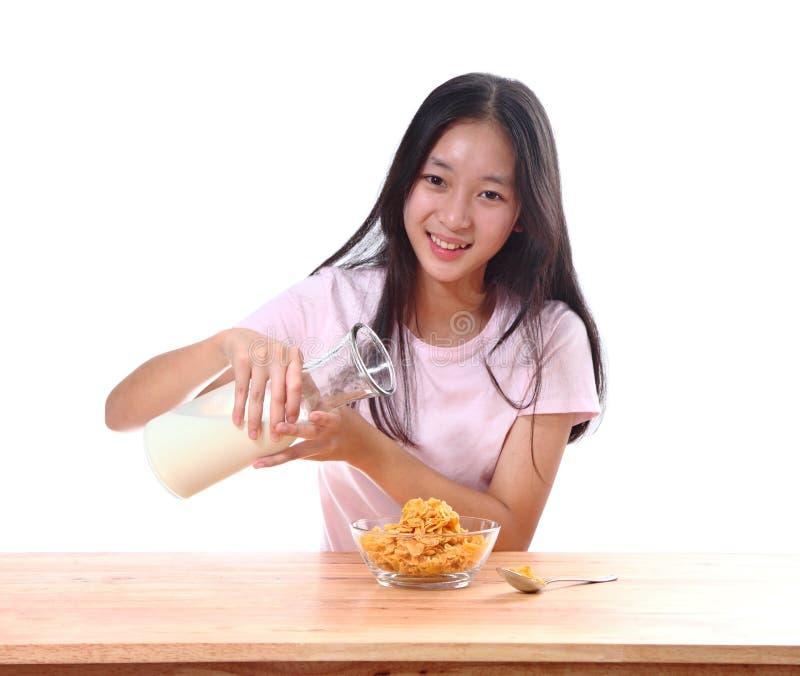 Fille mignonne ayant des céréales de petit déjeuner avec du lait dans la cuisine photos libres de droits