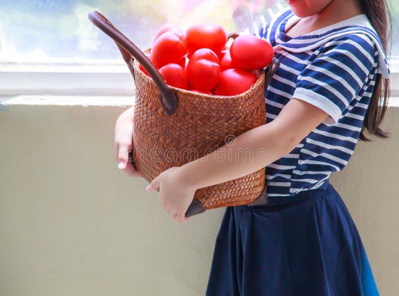 Fille mignonne caucasienne dans la robe rayée de bleu marine, panier rouge de transport de coeurs pour encourager la famille Sa g images stock