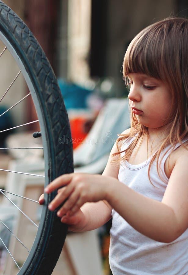 Fille mignonne curieuse regardant la roue de bicyclette photo stock
