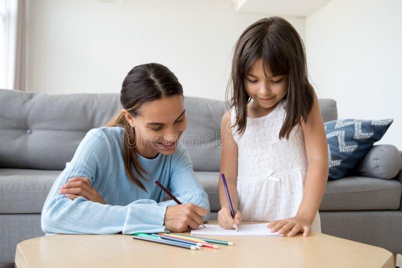 Fille mignonne d'enfant avec l'aspiration de maman avec les crayons colorés ensemble photos stock