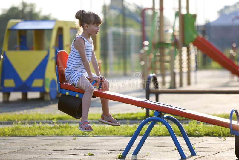 Fille mignonne d'enfant en bas âge dehors sur l'oscillation de bascule le jour ensoleillé d'été photographie stock