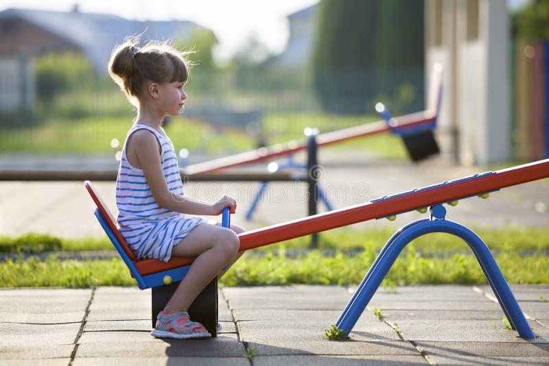 Fille mignonne d'enfant en bas âge dehors sur l'oscillation de bascule le jour ensoleillé d'été photos stock