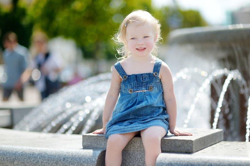 Fille mignonne d'enfant en bas âge jouant avec une fontaine de ville images stock