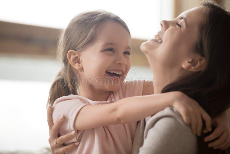 Fille mignonne d'enfant et maman de sourire riant embrassant la caresse ensemble images libres de droits