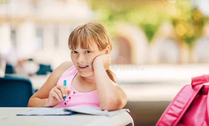 Fille mignonne d'enfant faisant des devoirs d'école dehors photos stock