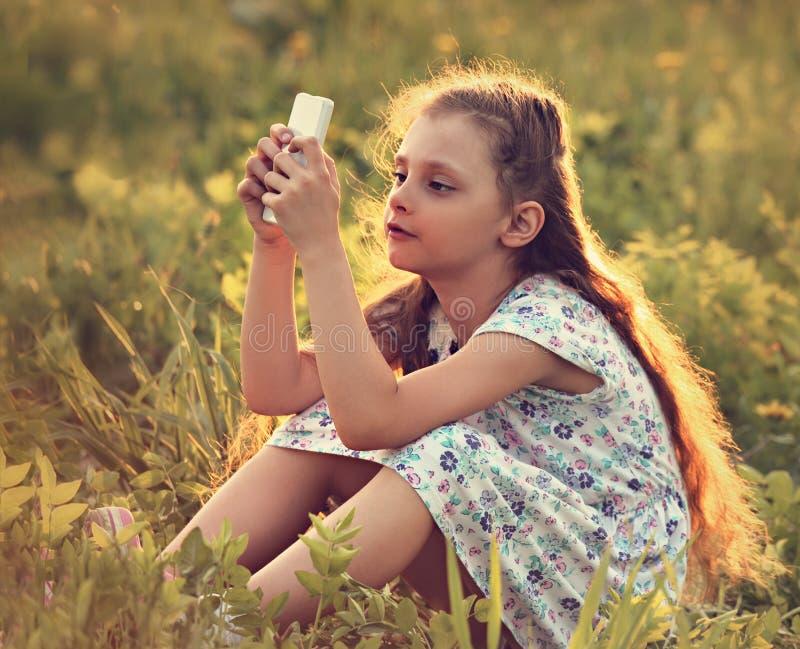 Fille mignonne d'enfant s'asseyant sur le verre et jouant au téléphone portable W photo libre de droits
