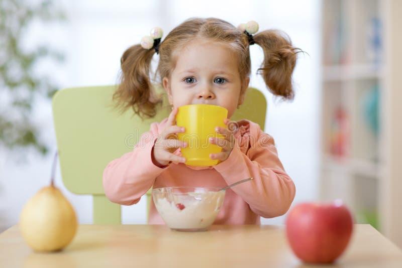 Fille mignonne d'enfant tenant le verre de l'eau à la maison photographie stock libre de droits