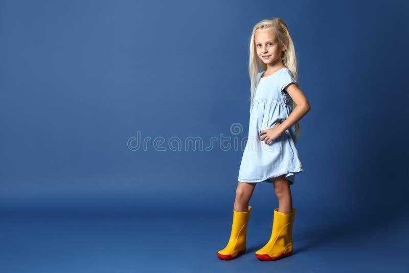 Fille mignonne dans des vêtements à la mode sur le fond de couleur photos libres de droits