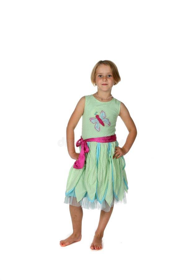 Fille mignonne dans la robe verte avec la main sur le gratte-cul photographie stock libre de droits