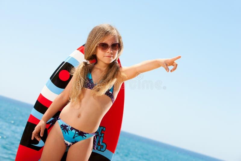 Fille mignonne dans le bikini se dirigeant avec le doigt à l'extérieur. photos libres de droits